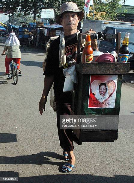 A man carries his 'portable kitchen' with a sticker on its side supporting candidate Indonesian President Megawati Sukarnoputri while looking for...