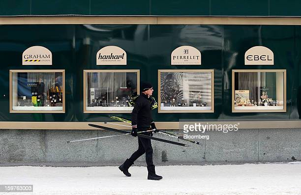 A man carries his ski's past a luxury watch store in the town of Davos Switzerland on Saturday Jan 19 2013 Next week the business elite gather in the...