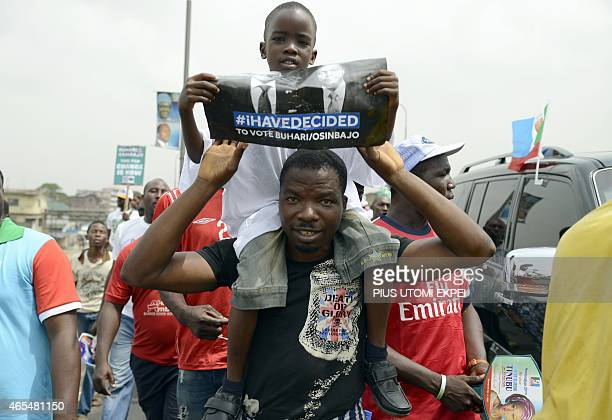 A man carries his son holding a poster with pictures of opposition APC presidential candidate Mohammadu Buhari and running mate Yemi Osinbaja during...