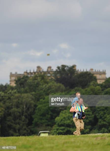 A man carries his son on his shoulders as he walks across the campsite in the grounds of Harewood House in Yorkshire as visitors get ready for the...