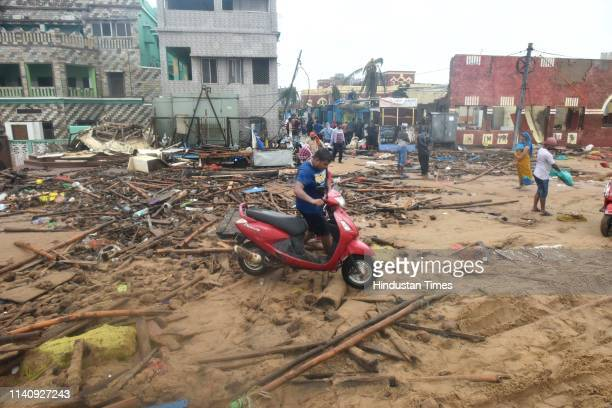 A man carries his vehicle amid the devastation after the onset of cyclone Fani at Puri beach on May 3 2019 in Puri India Cyclone Fani on Friday...