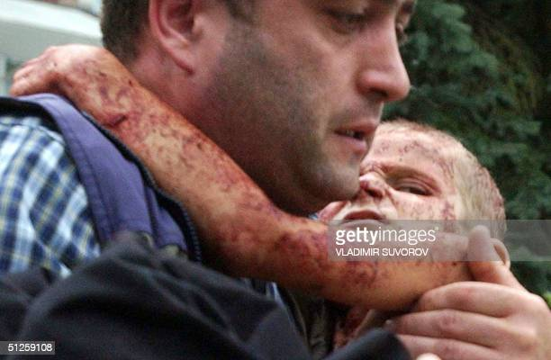 OUT* A man carries injured boy during the rescue operation in the school garden in the town of Beslan North Ossetia 03 September 2004 One hundred and...