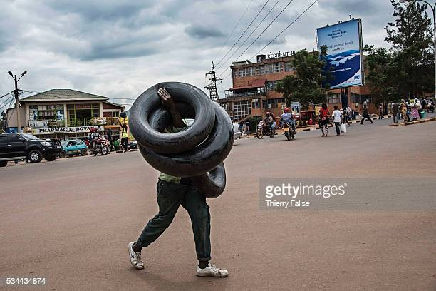 A man carries inner tubes across a street in a Kigali popular district Kigali with a population of more than one million is Rwandas capital and main...