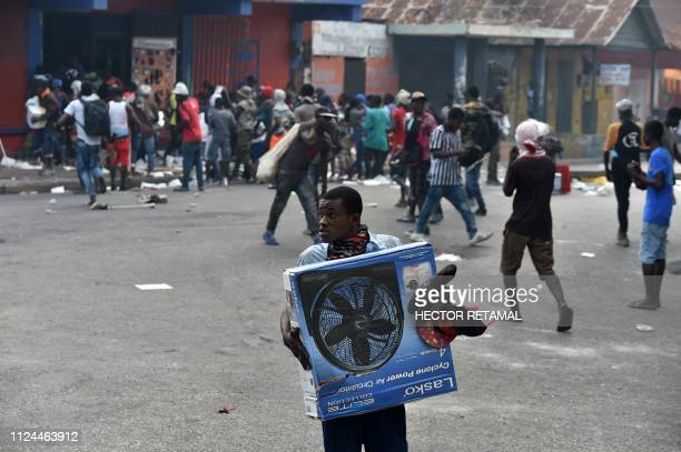 A man carries looted items from a store in the center of Haitian capital PortauPrince on February 12 as a sixth day of protests against Haitian...