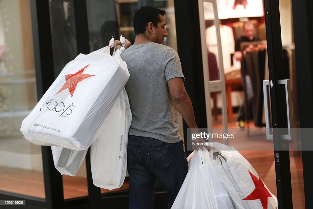 A man carries Macy's Inc. shopping bags while walking through the Fair Oaks Mall in Fairfax, Virginia, U.S., on Monday, Nov. 12. 2012. Sales at U.S. retailers probably fell in October for the first time in four months economists said before a report on Nov. 14. Photographer: Andrew Harrer/Bloomberg via Getty Images