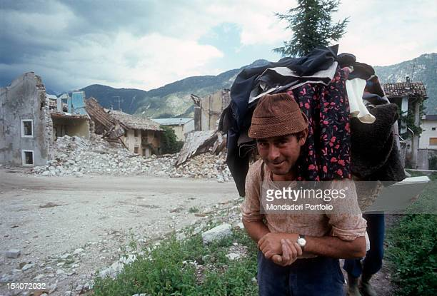 A man carries on his back a basket full of clothes taken from the ruins of their homes destroyed by the earthquake FriuliVenezia Giulia May 1976