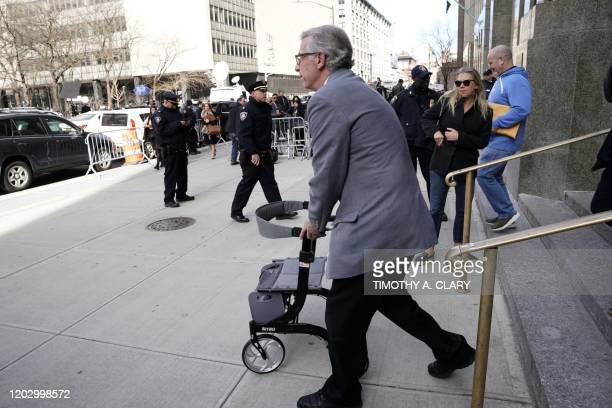 A man carries out the walker of Harvey Weinstein in front of the Manhattan Criminal Court on February 24 2020 in New York City Harvey Weinstein was...