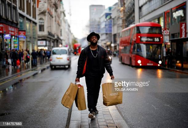 A man carries paper shopping bags as he waks along Oxford Street in London on November 26 2019 Black Friday is a sales offer originating from the US...