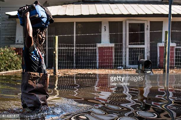 A man carries personal items through a flooded street caused by remnants of Hurricane Matthew on October 11 2016 in Fair Bluff North Carolina...
