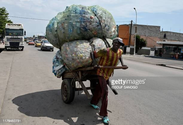 A man carries plastic bottles in the popular neighborhood of Abobo in the suburbs of Abidjan on November 2 2019