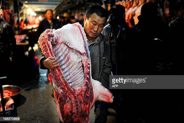 A man carries pork in a market in Hefei east China's Anhui province on May 9 2013 Inflation in China accelerated to 24 percent yearonyear in April...
