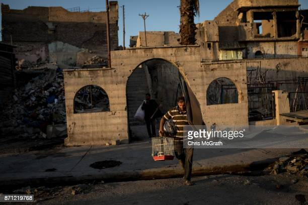 A man carries salvaged belongings in an outer neighborhood of the Old City in West Mosul on November 3 2017 in Mosul Iraq Five months after Mosul...
