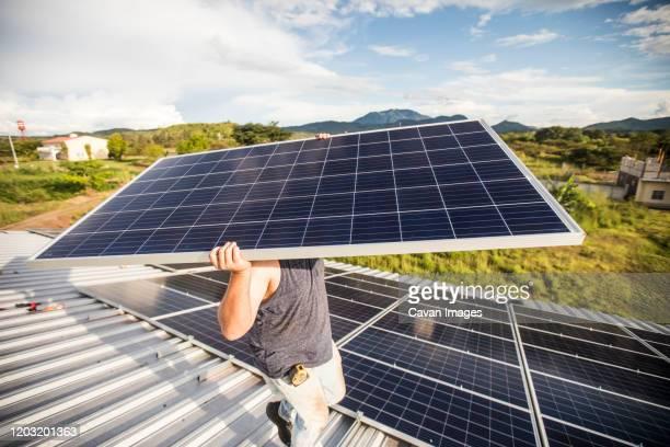 man carries solar panel over his head during installation. - steuerpult stock-fotos und bilder