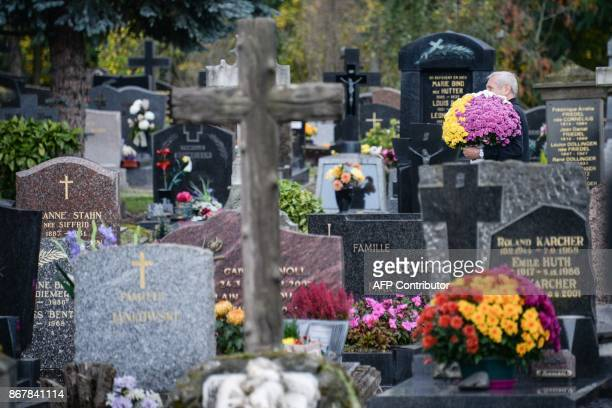 A man carries some flowers in a Strasbourg cemetery on October 29 ahead of the All Saints' Day on November 1 / AFP PHOTO / SEBASTIEN BOZON