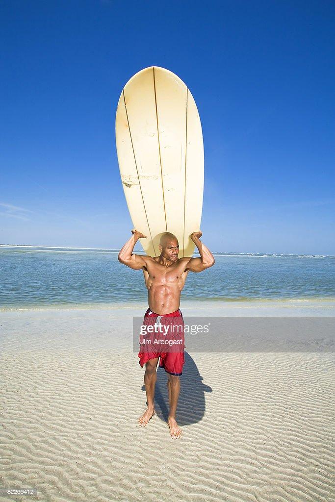 Man carries surfboard. : Stock Photo