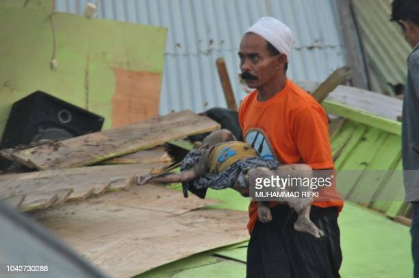 A man carries the body of a child after an earthquake and tsunami hit Palu on Sulawesi island on September 29 2018 Rescuers scrambled to reach...