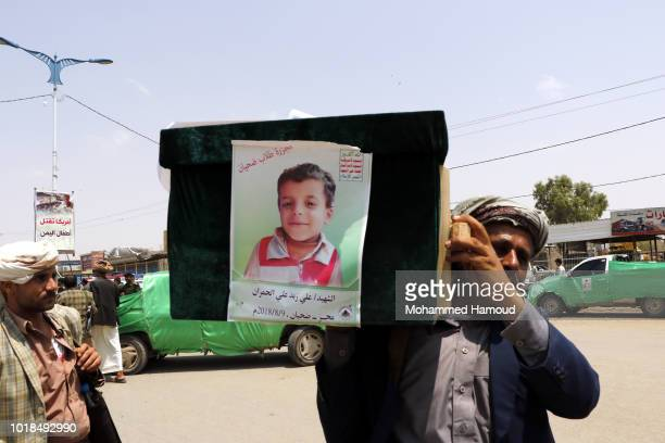 A man carries the coffin of a child at the funeral procession for those killed in an airstrike on a bus carried out last week by a warplane of the...