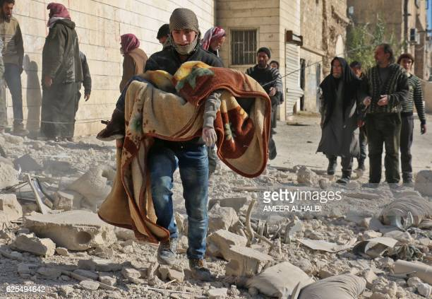 A man carries the covered body of a boy following a reported barrel bomb attack on the Bab alNairab neighbourhood of the northern Syrian city of...