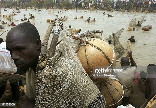 A man carries the gourd his uses as a flotation device during the Argungu Fishing Festival on March 20 2004 in Argungu Nigeria The Argungu Fishing...