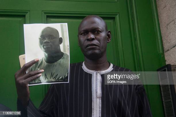 Man carries the photo of Mame Mbaye in the portal where he died Protest against institutional racism took place at Nelson Mandela square one year...