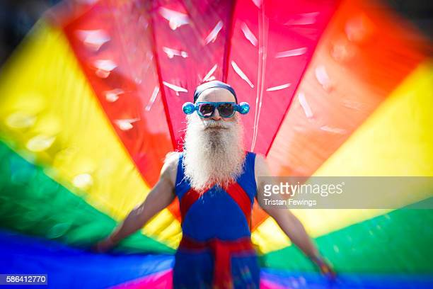 A man carries the rainbow flag as he takes part in the Brighton Pride Parade on August 6 2016 in Brighton England