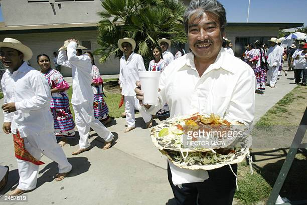 A man carries traditional Oaxcan dishes during the celebrations of the Guelaguetza in Los Angeles 03 August 2003 The Guelaguetza a zapotec word...