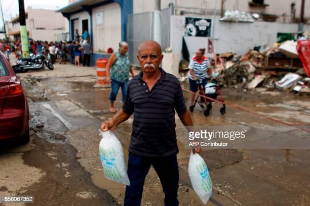 A man carries two bags of ice he bought at a local ice plant in the aftermath of Hurricane Maria in Arecibo Puerto Rico September 30 2017 US military...