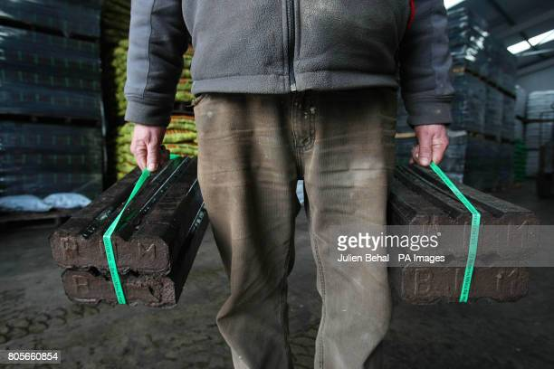 A man carries two bales of Peat Briquettes in Ahern Fuels in Urlingford CoKilkenny on Budget day when the Government has signalled it will introduce...