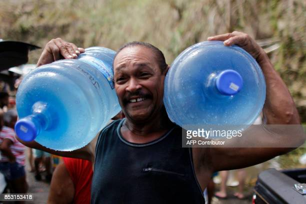 A man carries two water jugs filled with water collected from a natural spring created by the landslides in a mountain next to a road in Corozal west...