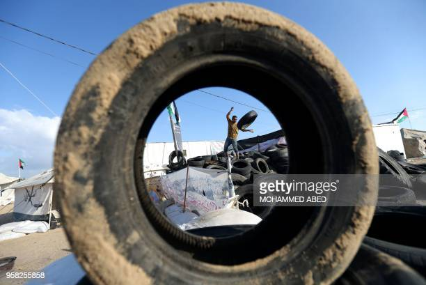 Man carries tyres to be burnt as Palestinians prepare to demonstrate along the border with the Gaza strip, east of Jabalia on May 14, 2018. - The US...