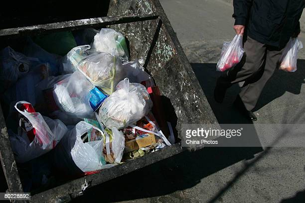 A man carries vegetables wrapped in plastic bags as he walks past a dust cart on March 13 2008 in Beijing China The Chinese government has announced...