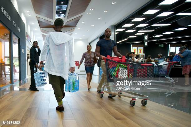 A man carries water bottles as people buy provisions on September 18 in PetitBourg on the Fench Caribbean island of Guadeloupe as Hurricane Maria...