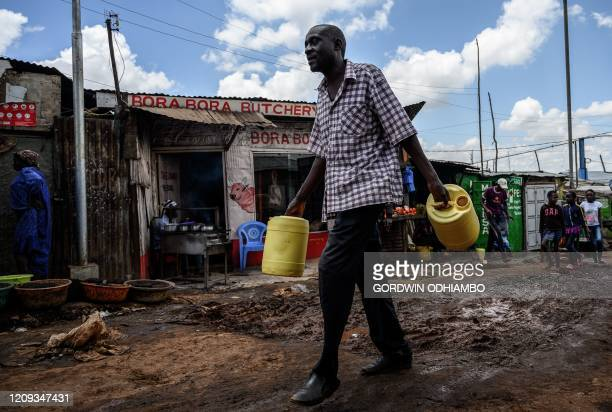 A man carries water jerrycans to fetch free water distributed by the Kenyan government at Kibera slum in Nairobi Kenya on April 7 2020 President...