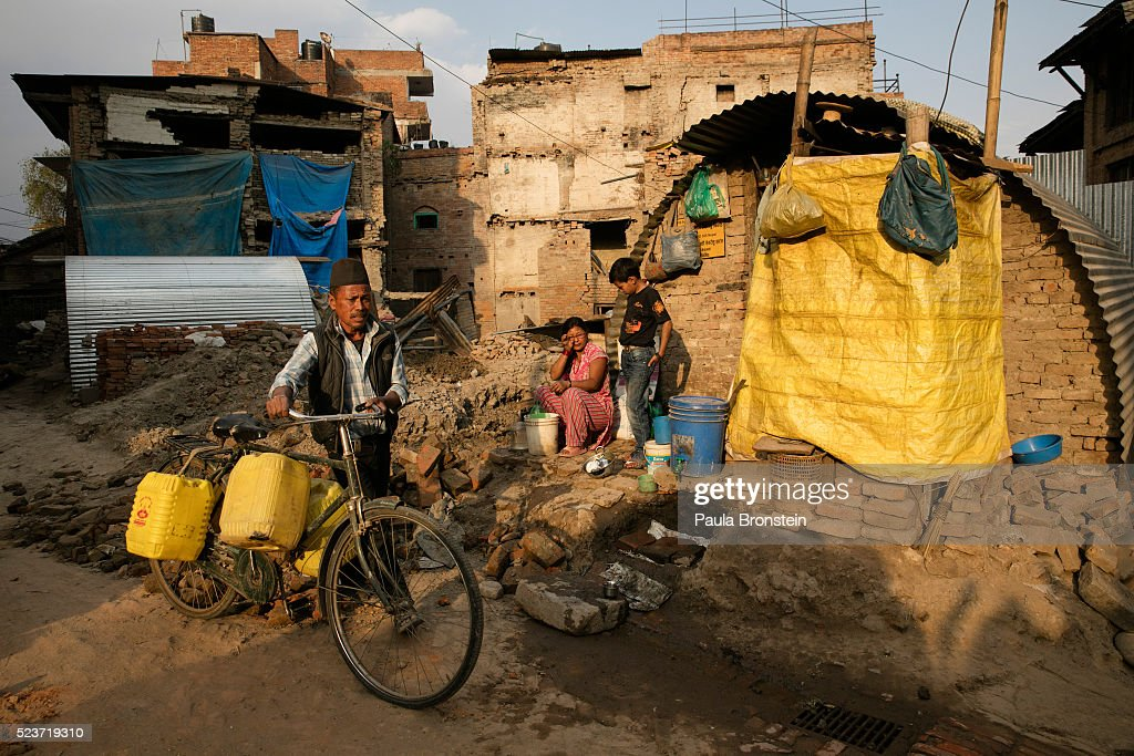 A man carries water past Nischal,11, and his mother Laxmi who are in front of their makeshift home in Bhaktapur on April 23, 2016 in Kathmandu, Nepal. The 7.8-magnitude earthquake struck Nepal close to midday on April 25 last year, killing an estimated 9,000 people. Reports suggest the government promised 2,000USD to affected households but has only paid out a fraction of the amount so far and an estimated 660,000 families are still living in sub-standard temporary shelter or unsafe accommodations one year later.