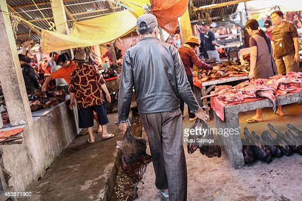 A man carries wild boar thigh at Langowan traditional market on August 9 2014 in Langowan North Sulawesi The Langowan traditional market is famous...