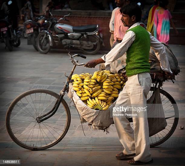 man carring bananas on bicycle in durbar square. - カトマンズ ダルバール広場 ストックフォトと画像