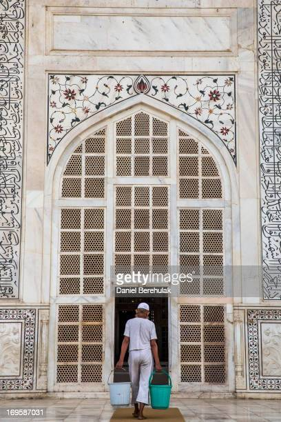 A man carrries buckets of water into the mausoleum at the Taj Mahal on May 28 2013 in Agra India Completed in 1643 the mausoleum was built by the...