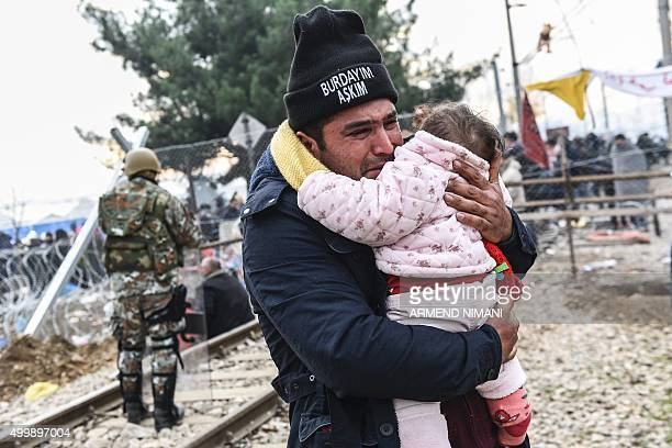 TOPSHOT A man carrying a baby cries after crossing the GreekMacedonian border with other migrants and refugees near the town of Gevgelija on December...