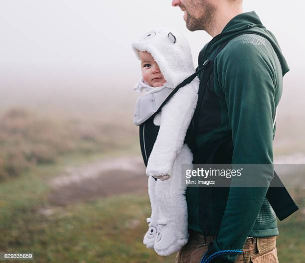 A man carrying a baby in a baby carrier on his chest, outdoors on a misty autumn day