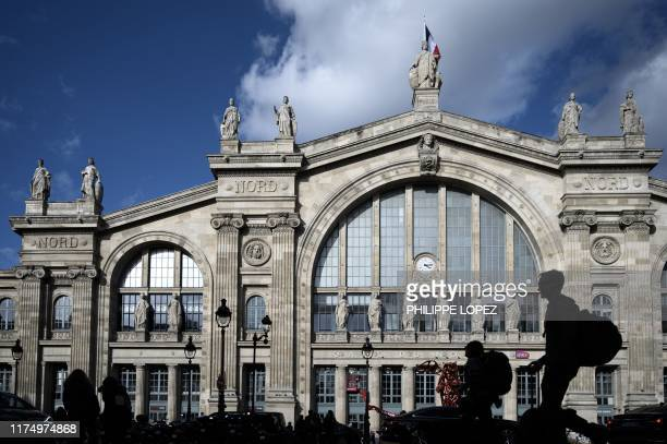 Man carrying a backpack walks past the historic facade of the Gare du Nord train and metro station in Paris on October 10, 2019.