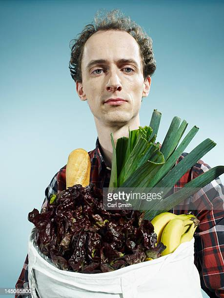a man carrying a bag of groceries - leaf lettuce stock photos and pictures