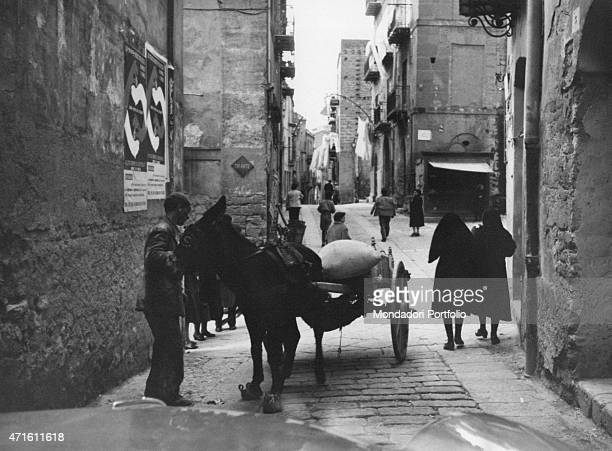 'A man carrying a bag on a cart drawn by a donkey Agrigento December 1956 '