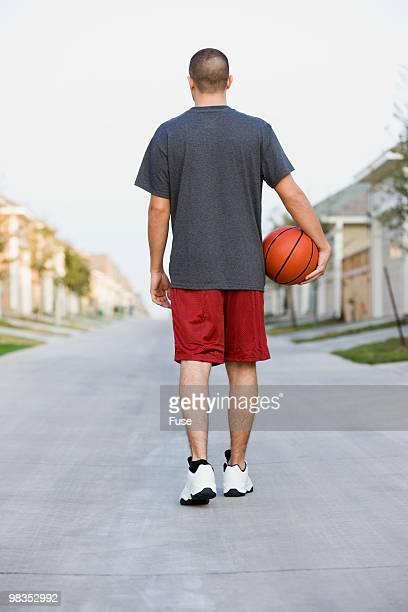 man carrying a basketball - pantaloncini grigi foto e immagini stock