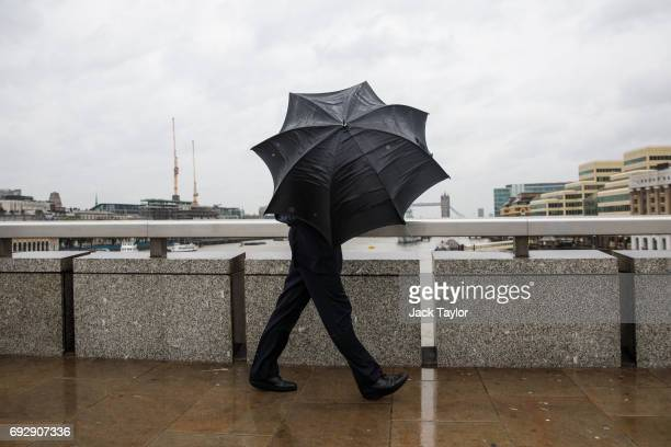 A man carrying a black umbrella walks across London Bridge during heavy rain and strong winds on June 6 2017 in London England