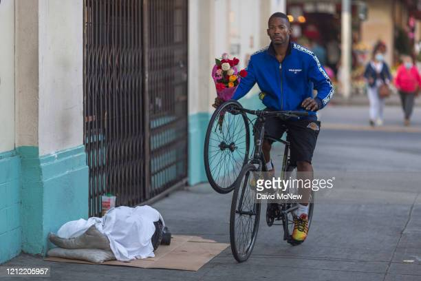 Man carrying a bouquet of discarded flowers he collected passes near a homeless person sleeping on the sidewalk as businesses in the flower district...