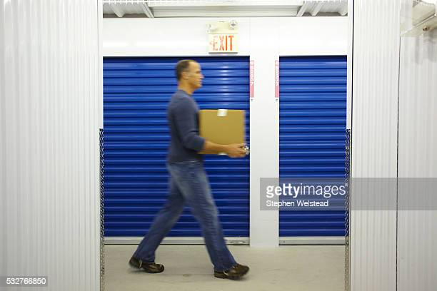 man carrying a box in a storage facility - self storage stock pictures, royalty-free photos & images