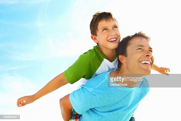 Man carrying a boy on his back both are smiling