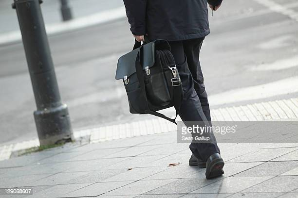 A man carrying a briefcase walks along Unter den Linden avenue in Mitte district on October 12 2011 in Berlin Germany Mitte district is home not only...