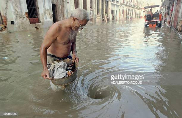 A man carrying a bucket full of trash comes closer to a whirlpool formed by the water flooding through the street sewage 24 October 2005 in Havana...