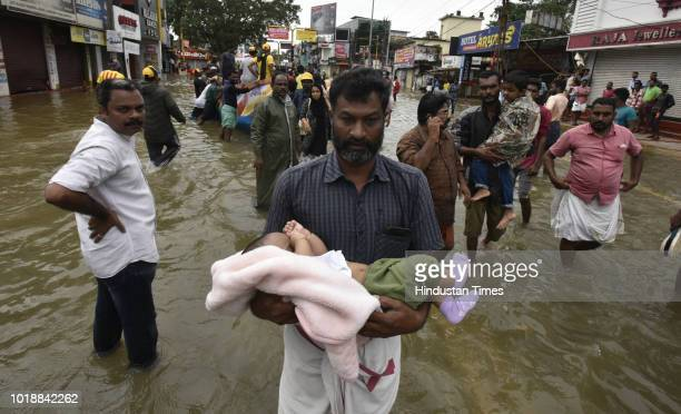 A man carrying a child through the flood waters to a safe place at Panadala on August 18 2018 in district Pathanamthitta India The flooding described...